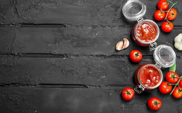Molho de tomate em uma jarra de tomates. em preto rústico
