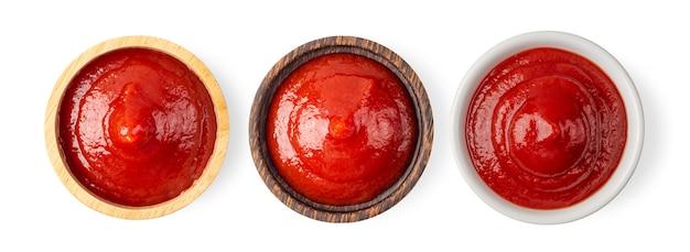 Molho de tomate em uma tigela de madeira isolado na superfície branca. vista do topo