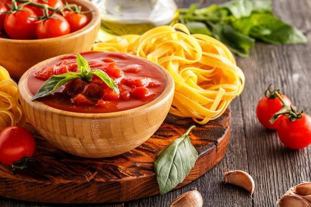 Molho de tomate, macarrão, tomate, alho, azeite na velha de madeira.