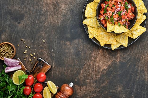 Molho de tomate mexicano tradicional com nachos e ingredientes de tomate, chile, alho, cebola
