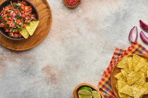 Molho de tomate mexicano tradicional com nachos e tomates de ingredientes, pimenta, alho, cebola em fundo de pedra de ardósia clara. conceito de comida latino-americana e mexicana. brincar.