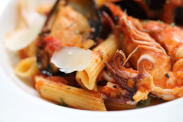 Molho de tomate penne arabiata com frutos do mar no estilo vintage de fundo de madeira