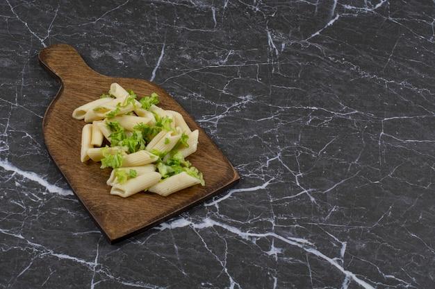 Molho de vegetais verdes de macarrão penne na tábua de madeira.