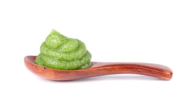 Molho de wasabi em uma colher de madeira, isolada no branco. molho picante asiático.