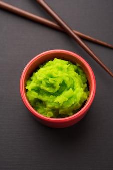 Molho de wasabi verde ou pasta em uma tigela, com pauzinhos ou colher sobre um fundo colorido simples. foco seletivo
