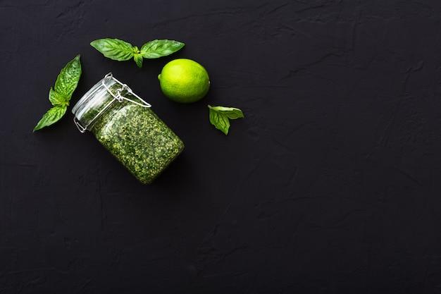 Molho pesto caseiro, manjericão verde, limão em fundo escuro de cimento. molho pesto verde italiano em frasco de vidro para macarrão, espaguete. alimentação vegetariana saudável. vista superior, plana leiga com espaço de cópia para o texto.