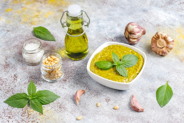 Molho pesto de manjericão italiano com ingredientes culinários para cozinhar.