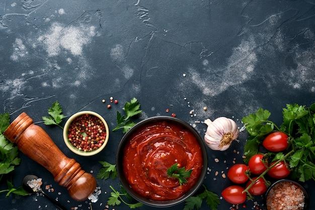 Molho picante de ketchup de tomate em uma tigela preta com especiarias e tomates frescos em uma ardósia escura, pedra ou fundo de concreto. vista superior com espaço de cópia.