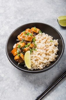 Molho teriyaki cubos de frango suculento com arroz - almoço delicioso estilo asiático sobre fundo claro, vista superior