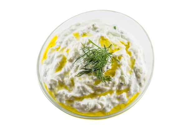 Molho tzatziki em uma tigela de vidro, isolado no fundo branco.