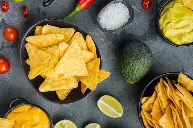 Molhos nachos e guacamole e queijo, em mesa cinza, vista de cima ou plano