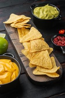Molhos nachos e guacamole e queijo, em velha mesa de madeira