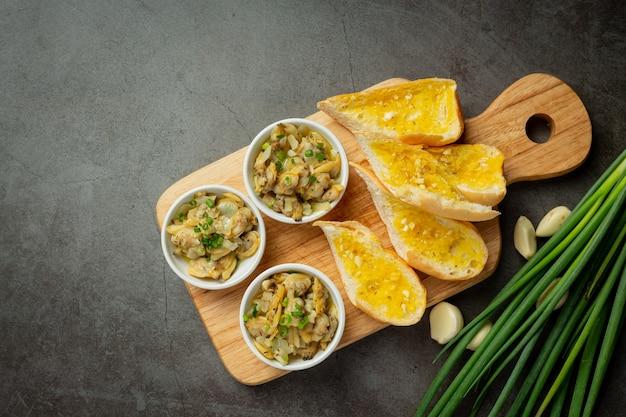 Molusco assado com alho e manteiga servido com pão de alho em fundo escuro