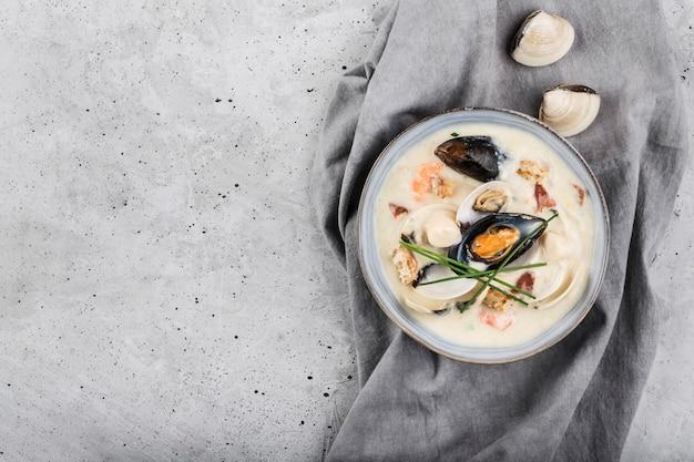 Molusco ensopado em um prato cinza. os principais ingredientes são mariscos, caldo, manteiga, batata e cebola.