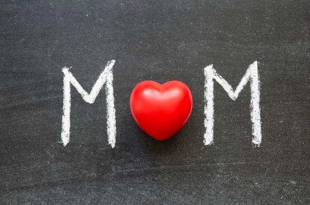 Mom palavra escrita à mão no quadro negro da escola com um coração vermelho como uma letra o