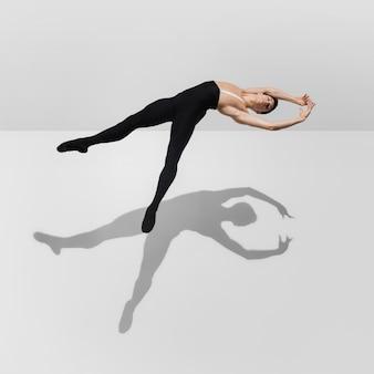 Momento de captura. elegante jovem atleta do sexo masculino no fundo branco do estúdio com sombras em salto, vôo do ar. modelo de ajuste esportivo em movimento e ação. musculação, estilo de vida saudável, conceito de estilo.