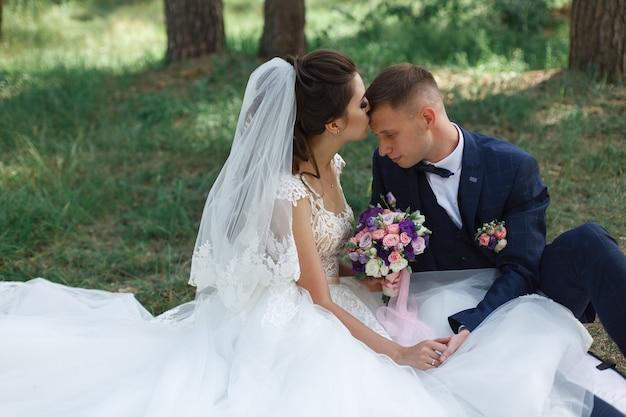 Momento de casamento romântico. casal jovem feliz casamento abraçando ao ar livre no parque verde. noiva emocional em vestido branco e noivo de terno na caminhada na primavera.