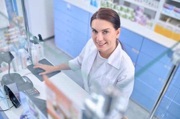 Momento de trabalho. mulher alegre e afável com sorriso cheio de dentes e jaleco atrás da caixa registradora em uma farmácia brilhante