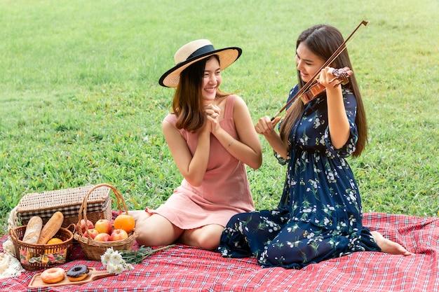 Momento doce do amor. retrato de casal homossexual asiático tocando violino e piquenique no parque. conceito lgbt leasbian.