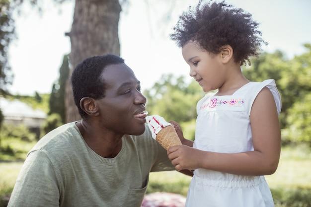 Momento doce. garoto fofo de cabelos cacheados tomando sorvete e passando um tempo com o pai