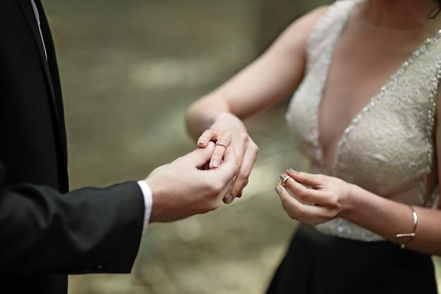Momento em que o noivo coloca o anel na mão de uma jovem noiva