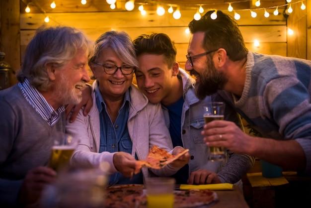 Momento engraçado de família no jantar comendo pizza e bebendo cerveja juntos - noite de natal e festa de ano novo