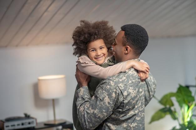 Momento feliz. menina afro-americana nos braços de um militar em pé, emocional, feliz em casa, no quarto