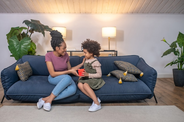 Momento feliz. menina bonita de pele escura e cacheada dando um presente em uma caixa vermelha para uma jovem mãe feliz sentada no sofá em casa