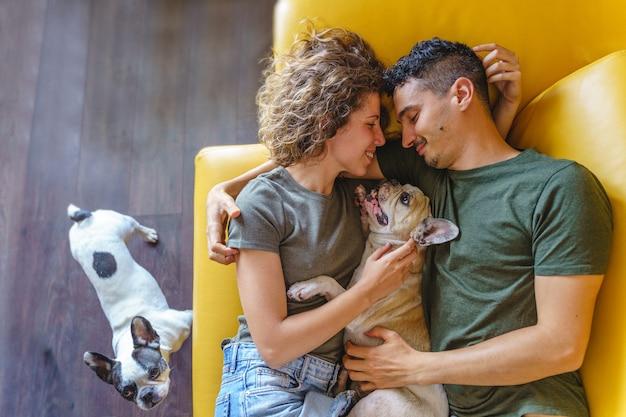 Momento íntimo de casal com animais de estimação em casa no sofá. vista superior vertical brincando com animais de estimação.