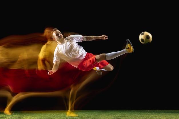 Momento. jovem homem caucasiano de futebol ou jogador de futebol em roupas esportivas e botas, chutando a bola para o gol em luz mista na parede escura. conceito de estilo de vida saudável, esporte profissional, hobby.