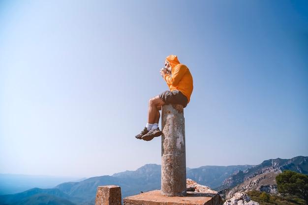 Momento solitário. o homem se senta no topo da rocha e observa o vale tomando um café