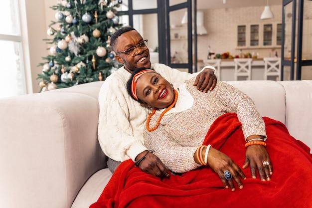 Momentos agradáveis. casal simpático e encantado, sorrindo enquanto desfruta do conforto de sua casa