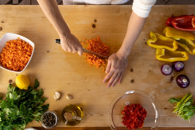 Momentos da vida cotidiana na culinária mediterrânea: vista de baixo ângulo de uma jovem cozinheira que corta cenouras com vários legumes em sua mesa de trabalho de madeira clara com efeito bokeh