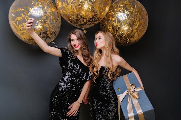 Momentos de festa feliz de duas mulheres elegantes fazendo selfie. vestido preto luxuoso, cabelos longos cacheados, grandes balões com enfeites dourados, presente, se divertindo, sorrindo.
