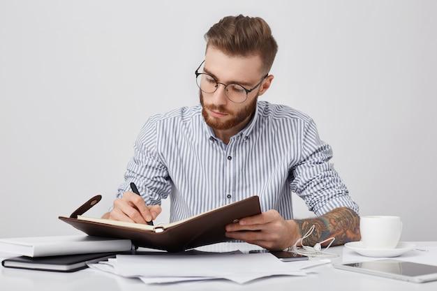 Momentos de trabalho. homem tatuado sério e concentrado, usando camisa formal e óculos redondos