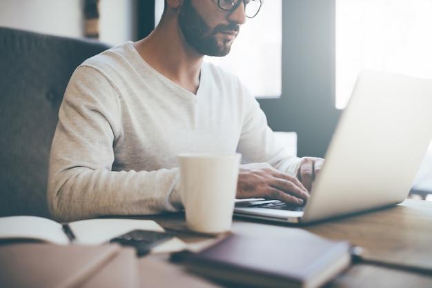 Momentos de trabalho. imagem recortada de jovem confiante usando óculos trabalhando em um laptop enquanto está sentado no escritório ou em um café