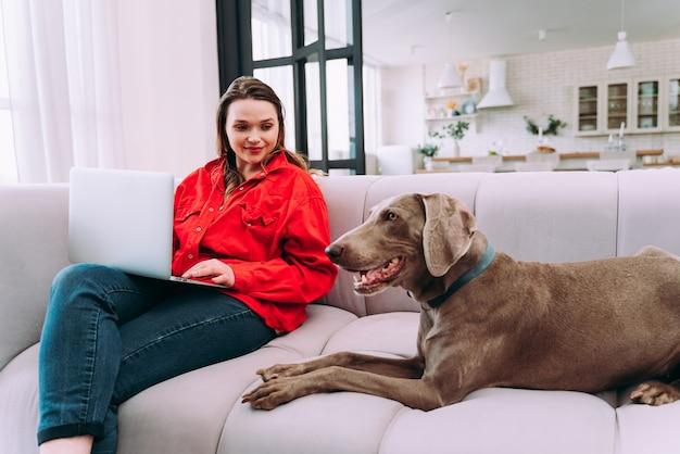 Momentos do estilo de vida de uma jovem em casa. mulher brincando com seu cachorro na sala de estar