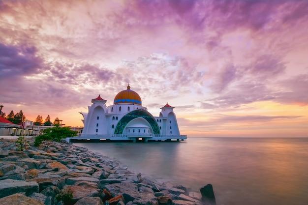 Momentos do nascer do sol na mesquita do estreito de malaca (masjid selat melaka), é uma mesquita localizada na ilha de malaca, construída pelo homem, perto da cidade de malaca, na malásia