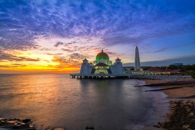 Momentos do pôr do sol na mesquita do estreito de malaca (masjid selat melaka), é uma mesquita localizada na ilha de malaca, construída pelo homem, perto da cidade de malaca, na malásia