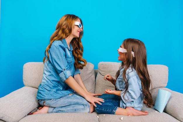 Momentos doces da bela jovem mãe se divertindo com a filha no sofá isolado sobre fundo azul. estilo moderno em roupas jeans, óculos 3d, expressando positividade familiar
