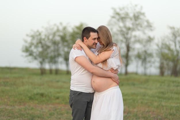 Momentos felizes de gravidez. um marido amoroso com sua esposa grávida no ar fresco longe da cidade.