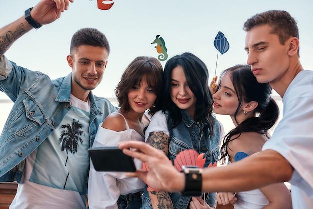 Momentos felizes, grupo de amigos felizes fazendo uma selfie durante a festa no telhado