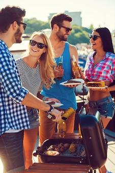 Momentos felizes juntos. grupo de jovens alegres segurando pratos enquanto um homem lhes põe comida de churrasco