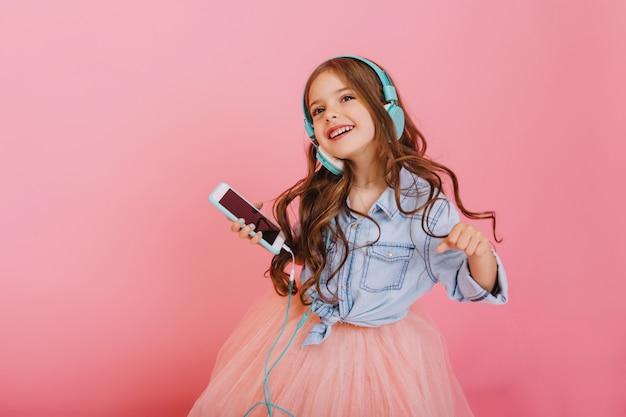 Momentos lindos de criança curtindo música através de fones de ouvido, dançando com o telefone isolado no fundo rosa. expressando emoções positivas verdadeiras de criança feliz na moda no entretenimento