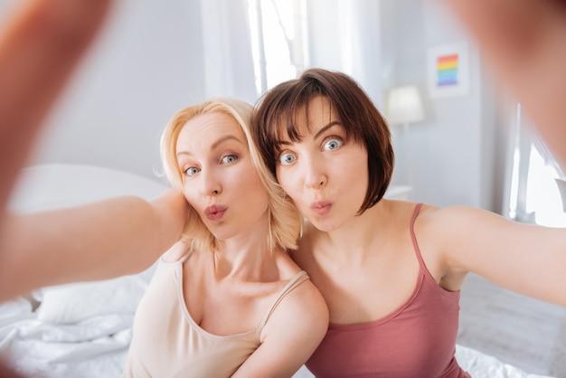 Momentos memoráveis. mulheres positivas e alegres juntas tirando uma foto enquanto olham para a câmera