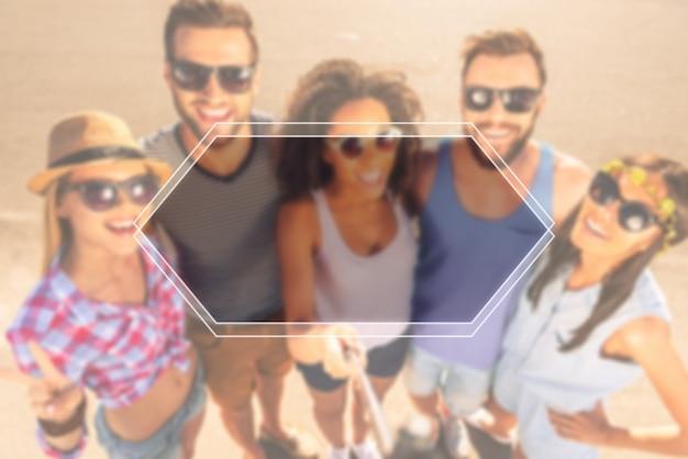 Momentos que valem a pena lembrar. vista superior de um grupo de jovens alegres fazendo selfie enquanto estão juntos ao ar livre