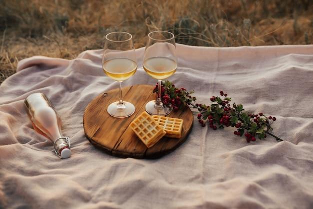 Momentos românticos de verão ao pôr do sol com dois copos de vinho branco, garrafa e sobremesa.