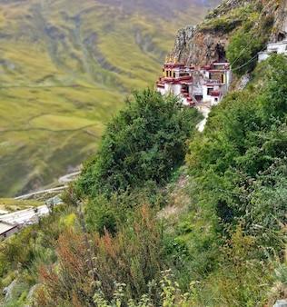 Monastério budista de drak yerpa do tibetano no penhasco nas montanhas de tibet.
