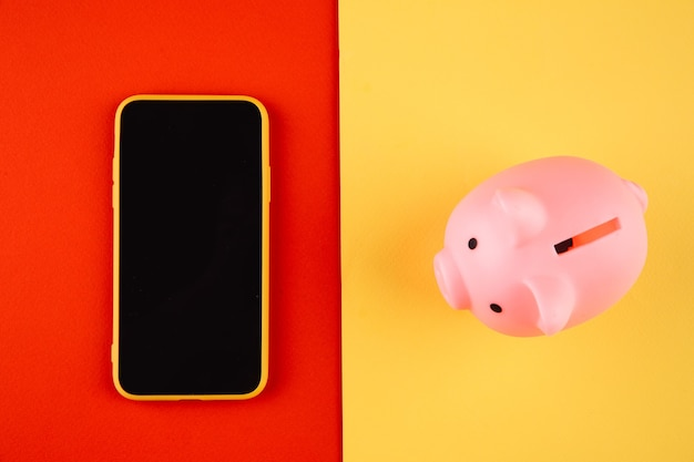Moneybox e telefone celular. conceito de finanças e orçamento. cofrinho na cor rosa com gadgets em fundo colorido.