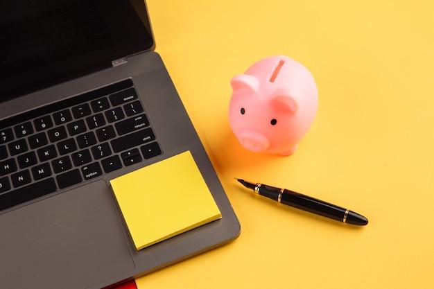 Moneybox perto de laptop e nota auto-adesiva amarela, lugar para texto. conceito de finanças e orçamento. cofrinho na cor rosa com gadgets e artigos de papelaria em fundo colorido.